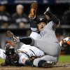 New York Yankees\' Ichiro Suzuki, right, of Japan, leaps past Baltimore Orioles catcher Matt Wieters to score a run on a double by Robinson Cano in the first inning of Game 2 of the American League division baseball series on Monday, Oct. 8, 2012, in Baltimore. (AP Photo/Nick Wass)