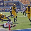 West Virginia\' Ishmael Banks (34) reaches over the goal line for touchdown after returning an interction 58-yard for the score during the first quarter of an NCAA college football game Oklahoma State in Morgantown, W.Va., on Saturday, Sept. 28, 2013. (AP Photo/Tyler Evert) ORG XMIT: WVTE101