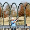Yukon city worker Nick Rice strings Christmas lights on a bridge at Chisholm Trail Park.