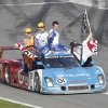 Juan Pablo Montoya, of Colombia, drives the Ganassi Racing BMW Riley down pit road with teammates on the car, from left, Charlie Kimball, Scott Pruett, Memo Rojas, of Mexico, and team owner Chip Ganassi waving the checker flag after winning the Grand-Am Series Rolex 24 hour auto race at Daytona International Speedway, Sunday, Jan. 27, 2013, in Daytona Beach, Fla. (AP Photo/David Graham)