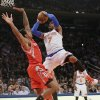 New York Knicks\' Carmelo Anthony (7) shoots over Houston Rockets\' Greg Smith during the first half of an NBA basketball game Thursday, Nov. 14, 2013, in New York. Smith was hurt on the play. (AP Photo/Frank Franklin II)