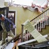 Bob Haslam navigates his way down stairs as he helps remove items from his daughter\'s home that was heavily damaged in the Oak Tree addition on Wednesday, Feb. 11, 2009, after a tornado hit the area on Tuesday in Edmond, Okla. PHOTO BY CHRIS LANDSBERGER, THE OKLAHOMAN