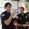 Photo - SB-242 : MOVIE: Two clueless cops, Officer Slater (Bill Hader, left) and Officer Michaels (Seth Rogen, right) check out the identification of McLovin, the 25-year-old Hawaiian organ donor, in