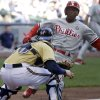 Photo - Milwaukee Brewers catcher Jonathan Lucroy tags out Philadelphia Phillies' Jimmy Rollins at home during the seventh inning of a baseball game Thursday, July 10, 2014, in Milwaukee. Rollins tried to score from third on a ball hit by Marlon Byrd. (AP Photo/Morry Gash)