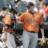 Photo - Houston Astros relief pitcher Chad Qualls, right, celebrates with catcher Carlos Corporan after the Astros defeated the Chicago White Sox 11-7 in a baseball game in Chicago on Sunday, July 20, 2014. (AP Photo/Nam Y. Huh)