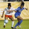 Photo - Virginia's Morgan Stith, left, battles UCLA's Caprice Dydasco for the ball during the first half of an NCAA college soccer semifinal match at the Women's College Cup tournament in Cary, N.C., Friday, Dec. 6, 2013. (AP Photo/Ellen Ozier)