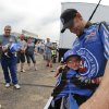 Photo - Funny Car driver Robert Height gets a hug from 8-year-old fan Lincoln Thompson prior to his first run of the day at the NHRA Kansas Nationals drag races at Heartland Park in Topeka, Kan., on Friday, May 23, 2014. (AP Photo/Topeka Capital-Journal,Chris Neal)