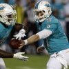 Photo - Miami Dolphins quarterback Ryan Tannehill (17) passes to running back Lamar Miller (26) during the first half of an NFL preseason football game against the Tampa Bay Buccaneers, Saturday, Aug. 24, 2013, in Miami Gardens, Fla. (AP Photo/Lynne Sladky)