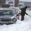 A soldier clears a car after a heavy snowstorm in Minsk, Belarus, Saturday, March 16, 2013. (AP Photo/Sergei Grits)