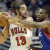 Photo - Chicago Bulls center Joakim Noah (13) looks to a pass as Philadelphia 76ers forward Thaddeus Young, right, guards during the first half of an NBA basketball game in Chicago, Saturday, Jan. 18, 2014. (AP Photo/Nam Y. Huh)
