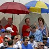 Fans use umbrellas to shield themselves from the sun while watching a spring training exhibition baseball game between the Toronto Blue Jays and the Atlanta Braves in Dunedin, Fla., Saturday, March 23, 2013. (AP Photo/Kathy Willens)