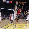 Houston Rockets\' James Harden (13) shoots between Golden State Warriors\' Klay Thompson (11), David Lee, center, and Andrew Bogut (12) during the first half of an NBA basketball game in Oakland, Calif., Tuesday, Feb. 12, 2013. (AP Photo/Marcio Jose Sanchez)