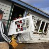 Christopher Hannafin, center, and Pete Duhamel, left, both of South Kingstown, R.I., salvage items, including a door, from a friend\'s cottage destroyed by Superstorm Sandy, on Roy Carpenter\'s Beach, in the village of Matunuck, in South Kingstown, Tuesday, Oct. 30, 2012. Sandy, the storm that made landfall Monday, caused multiple fatalities, halted mass transit and cut power to more than 6 million homes and businesses. (AP Photo/Steven Senne) ORG XMIT: RISR107