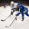 Vancouver Canucks\' Henrik Sedin, right, of Sweden, tries to stick handle around San Jose Sharks\' Justin Braun during the first period of an NHL hockey game, Thursday, Nov. 14, 2013 in Vancouver, British Columbia. (AP Photo/The Canadian Press, Darryl Dyck)