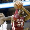 Oklahoma\'s Romero Osby, right, shoots past Missouri\'s Ricardo Ratliffe during the first half of an NCAA college basketball game Tuesday, Jan. 3, 2012, in Columbia, Mo. (AP Photo/L.G. Patterson) ORG XMIT: MOLG101