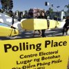 Photo -   A surfing class passes a sign for a polling place as voters head to the polls Tuesday, Nov. 6, 2012, in San Diego. After a grinding presidential campaign President Barack Obama and Republican presidential candidate, former Massachusetts Gov. Mitt Romney, yield center stage to American voters Tuesday for an Election Day choice that will frame the contours of government and the nation for years to come. (AP Photo/Gregory Bull)
