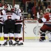 New Jersey Devils\' Peter Harrold, left, Andy Greene (6) and Patrik Elias, third from right, of the Czech Republic, celebrate Harrold\'s goal against Carolina Hurricanes goalie Dan Ellis (31) during the second period of an NHL hockey game in Raleigh, N.C., Thursday, March 21, 2013. (AP Photo/Gerry Broome)