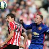 Photo - Manchester United's captain Wayne Rooney, right, vies for the ball with Sunderland's Santiago Vergini, left, during their English Premier League soccer match at the Stadium of Light, Sunderland, England, Sunday, Aug. 24, 2014. (AP Photo/Scott Heppell)