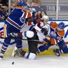 Colorado Avalanche\'s John Mitchell, center, is checked by Edmonton Oilers\' Ladislav Smid, left, as Sam Gagner (89) looks for the puck during the second period of their NHL hockey game, Monday, Jan. 28, 2013, in Edmonton, Alberta. (AP Photo/The Canadian Press, Jason Franson)