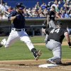 Photo - Milwaukee Brewers' Jonathan Lucroy is out at first with Chicago White Sox's Adam Dunn (44) covering on a ground ball during the first inning of an exhibition spring training baseball game Monday, March 10, 2014, in Phoenix. (AP Photo/Morry Gash)
