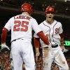 Photo -   Washington Nationals' Bryce Harper, right, low-fives Adam LaRoche after scoring on a home run by Ryan Zimmerman in the first inning of Game 5 of the National League division baseball series against the St. Louis Cardinals on Friday, Oct. 12, 2012, in Washington. (AP Photo/Alex Brandon)