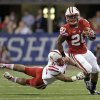 Wisconsin running back James White (20) runs out of the tackle attempt by Nebraska linebacker David Santos (41) during the first half of the Big Ten championship NCAA college football game Saturday, Dec. 1, 2012, in Indianapolis. (AP Photo/AJ Mast)