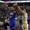 Photo - Philadelphia 76ers forward Thaddeus Young, center, drives between Indiana Pacers defenders Ian Mahinmi, left, and Luis Scola, of Argentina, during the first half of an NBA basketball game in Indianapolis, Monday, March 17, 2014. (AP Photo/AJ Mast)