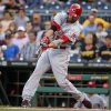 Photo - Cincinnati Reds' Joey Votto (19) drives in a run with a single off Pittsburgh Pirates starting pitcher Brandon Cumpton during the first inning of a baseball game in Pittsburgh Tuesday, June 17, 2014. (AP Photo/Gene J. Puskar)