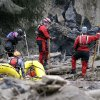 Searchers in boats and on foot look through debris following a deadly mudslide Tuesday, March 25, 2014, in Oso, Wash. At least 14 people were killed in the 1-square-mile slide that hit in a rural area about 55 miles northeast of Seattle on Saturday. Several people also were critically injured, and homes were destroyed. (AP Photo/Elaine Thompson)