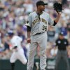 Photo - Pittsburgh Pirates starting pitcher Edinson Volquez, front, calls for new ball as Colorado Rockies' Brandon Barnes circles the bases after hitting a two-run home run in the fourth inning of a baseball game in Denver on Sunday, July 27, 2014. (AP Photo/David Zalubowski)