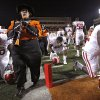 A member of the Oklahoma State marching band keeps playing while walking through praying members of the Oklahoma football team before the Bedlam college football game between the University of Oklahoma Sooners (OU) and the Oklahoma State University Cowboys (OSU) at Boone Pickens Stadium in Stillwater, Okla., Saturday, Nov. 27, 2010. Photo by Chris Landsberger, The Oklahoman