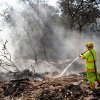Tuttle firefighter Joseph Lashbrook sprays water on smoldering embers and hot ashes behind a home that burned to the ground Tuesday after wildfires ravaged land and property that stretched from NE 50 on the south to Hefner Road on the north. The fire extended from Sooner Road to Midwest Blvd. Photo taken Wednesday, Aug. 31, 2011. Photo by Jim Beckel, The Oklahoman