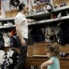 Photo - Buffalo Sabres left wing John Scott gets help cleaning out his locker from daughter Eva, 2, after players gathered for the last time on Monday, April 14, 2014, after the NHL hockey team clinched the NHL's worst record in Buffalo, N.Y. (AP Photo/Nick LoVerde)