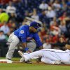 Photo -   Chicago Cubs third baseman Luis Valbuena tags out Washington Nationals' Michael Moore during the first inning of their baseball game at Nationals Park, Tuesday, Sept. 4, 2012, in Washington. (AP Photo/Richard Lipski)