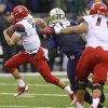 Photo - Arizona quarterback B.J. Denker, left, breaks away for a 33-yard run against Washington that set up a touchdown in the first half of an NCAA college football game, Saturday, Sept. 28, 2013, in Seattle. (AP Photo/Ted S. Warren)