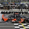 Driver Johnny Sauter (98) does a burnout as he celebrates winning the Kroger 250 NASCAR Truck series auto race at Martinsville Speedway in Martinsville, Va., Saturday, April 6, 2013. (AP Photo/Steve Helber)