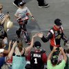 Photo - Driver Kurt Busch greets fans as he arrives for the NASCAR Sprint Cup series Coca-Cola 600 auto race at the Charlotte Motor Speedway in Concord, N.C., Sunday, May 25, 2014. Busch raced in the Indianapolis 500 earlier Sunday. (AP Photo/Gerry Broome)