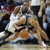 Memphis Grizzlies guard Mike Conley, top, tries to steal the ball from San Antonio Spurs guard Tony Parker in the second half of an NBA basketball game on Friday, Jan. 11, 2013, in Memphis, Tenn. Memphis won in overtime 101-98. (AP Photo/Lance Murphey)