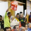 Photo - Carlos Hernandez-Sosa, center left, holds a sign in support of Seattle's $15 minimum wage measure, Monday, June 2, 2014, during a meeting of the Seattle City Council, which eventually passed the $15 minimum wage measure later in the meeting. (AP Photo/Ted S. Warren)