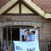 Photo - Uruguay's soccer player Luis Suarez, with his children Benjamin, left, and Delfina, waves to fans from his home, before the start of his team's World Cup round 16 match with Colombia, on the outskirts of Montevideo, Uruguay, Saturday, June 28, 2014. FIFA banned Suarez from all football activities for four months for biting an opponent at the World Cup, a punishment that rules him out of the rest of the tournament. (AP Photo/Matilde Campodonico)