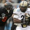 Oklahoma State\'s Daytawion Lowe (8) and Justin Gilbert (4) bring down Purdue\'s Akeem Shavers (24) during the Heart of Dallas Bowl football game between Oklahoma State University and Purdue University at the Cotton Bowl in Dallas, Tuesday, Jan. 1, 2013. Oklahoma State won 58-14. Photo by Bryan Terry, The Oklahoman