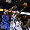 Photo - Memphis Grizzlies guard Michael Conley (11) drives to the basket by teammate Zach Randolph (50) and Oklahoma City Thunder's Ryan Bowen, left, during the second half of a preseason NBA basketball game Wednesday, Oct. 7, 2009, in Memphis, Tenn. (AP Photo/Lance Murphey) ORG XMIT: TNLM107