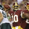 Photo - Washington Redskins quarterback Robert Griffin III (10) passes the ball during the first half of an NFL football game against the Philadelphia Eagles in Landover, Md., Monday, Sept. 9, 2013. (AP Photo/Patrick Semansky)