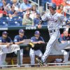 Photo - Virginia's Brandon Downes runs past the Mississippi dugout on his way to score on a two-run single hit by Robbie Coman in the fourth inning of an NCAA baseball College World Series game in Omaha, Neb., Saturday, June 21, 2014. (AP Photo/Ted Kirk)