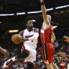 Photo - Miami Heat's Dwyane Wade (3) goes around Washington Wizards' Marcin Gortat (4) for two points during the first half of an NBA basketball game in Miami, Sunday, Nov. 3, 2013. (AP Photo/J Pat Carter)