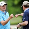 Photo - Justin Rose gets a fist bump after sinking a putt on the eighth hole during the Zurich Classic pro-am golf tournament at the TPC Louisiana on Wednesday, April 24 , 2013 in Avondale, La.  (AP Photo/Nola.com, Michael DeMocker) MAGS OUT; NO SALES; USA TODAY OUT; THE BATON ROUGE ADVOCATE OUT