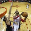 Photo - Houston Rockets' Dwight Howard (12) goes up to shoot as Portland Trail Blazers' Robin Lopez defends during the first quarter of an NBA basketball game on Sunday, March 9, 2014, in Houston. (AP Photo/David J. Phillip)