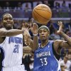 Photo - Orlando Magic's Maurice Harkless (21) passes the ball around Minnesota Timberwolves' Dante Cunningham (33) during the second half of an NBA basketball game in Orlando, Fla., Saturday, April 5, 2014. Orlando won 100-92. (AP Photo/John Raoux)