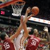 Photo - Iowa State forward Georges Niang, center, puts up a shot over Oklahoma forward Tyler Neal (15) and D.J. Bennett (31) during the first half of an NCAA college basketball game in Ames, Iowa, Saturday, Feb. 1, 2014. (AP Photo/Justin Hayworth)
