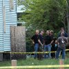 Law enforcement and FBI stand at the back of a boarded-up home where bodies were found earlier in the day Saturday, July 20, 2013 in East Cleveland, Ohio. Police say three bodies have been found in plastic bags in East Cleveland. Police Commander Mike Cardilli said a woman\'s body was found Friday in a garage and two other bodies were found Saturday _ one in a backyard and the other in the basement of a vacant house. (AP Photo/The Plain Dealer, Joshua Gunter) MANDATORY CREDIT; NO SALES